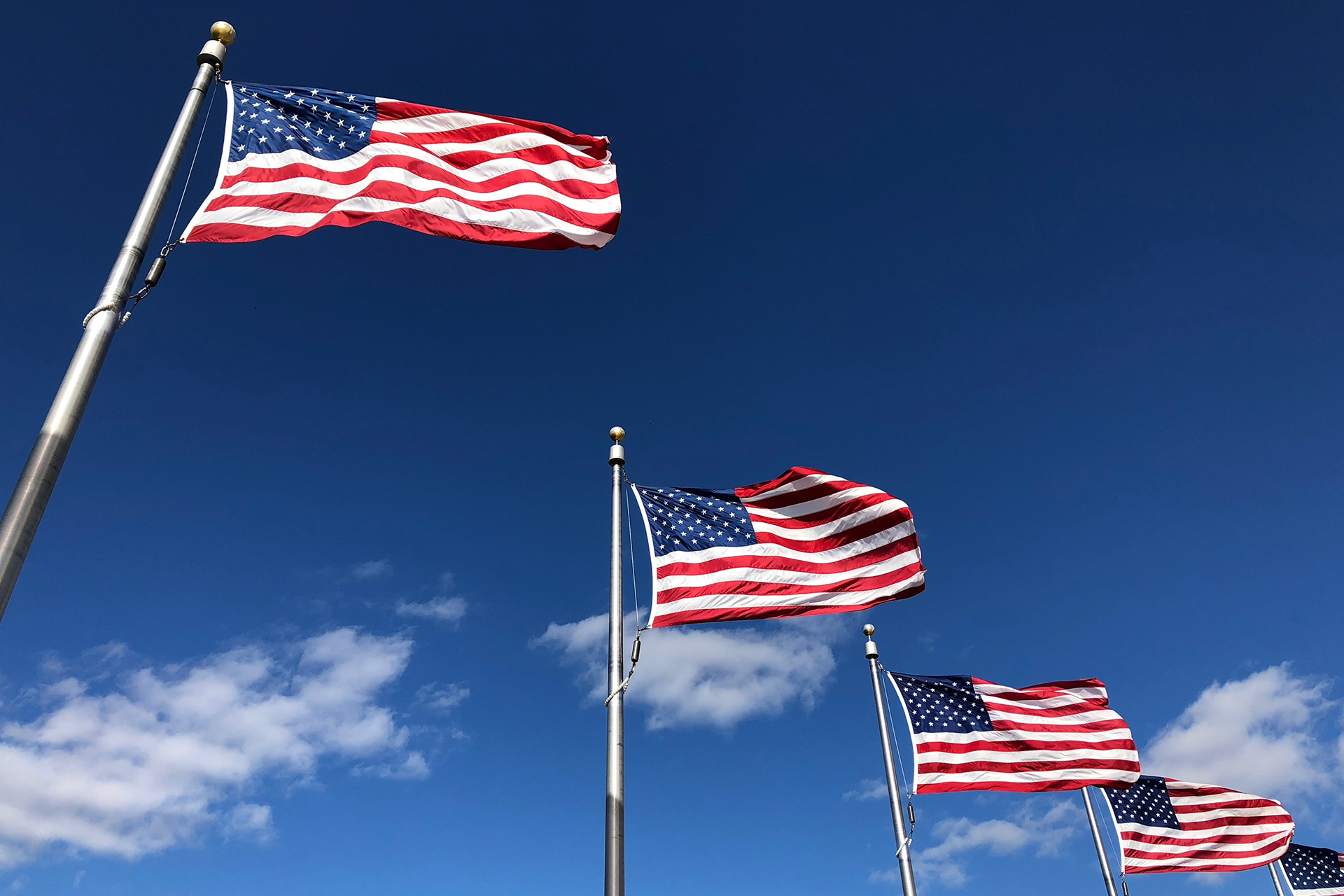 american flags under clear sky